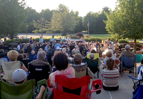 image of people in lawn chairs on steps with trees watching concert