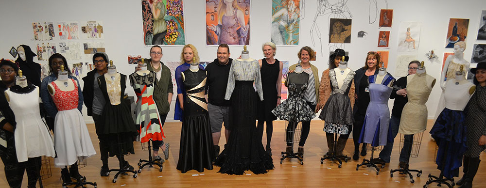 Group shot of Fashion Students with their work in the gallery
