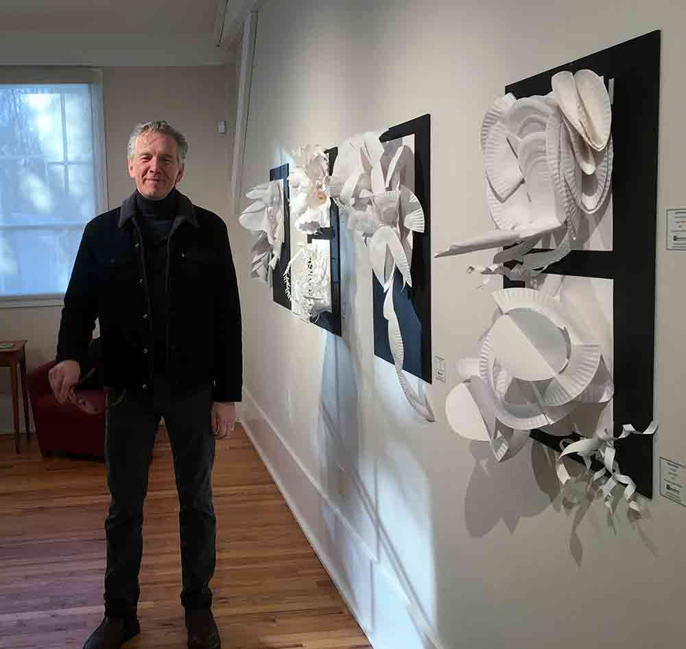 art professor with student 3-d paper sculptures hung on wall