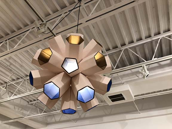 cardboard lamp in honeycomb shapes hanging from ceiling