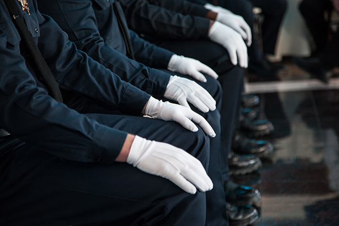 Seated officers wearing white gloves