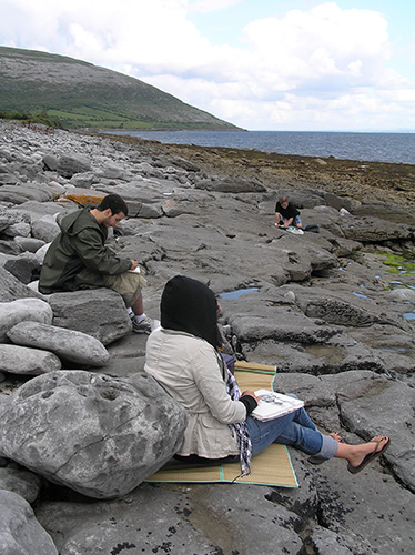 students drawing on rocky shore in Ireland