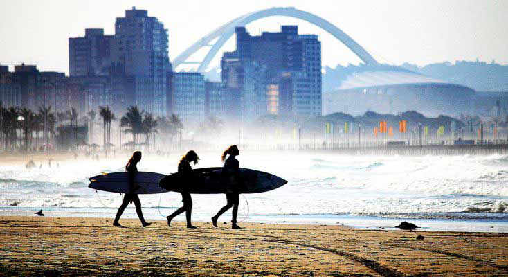 Surfers on beach with city of Durban behind them
