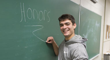 Student writing honors on chalkboard