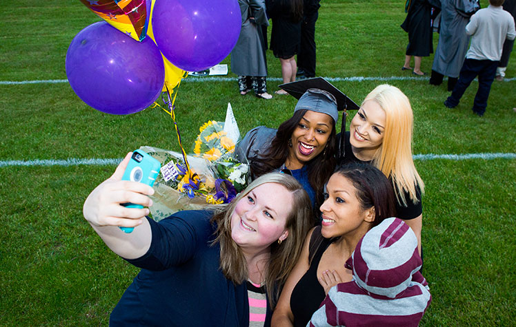 students posing for selfie with balloons at graduation