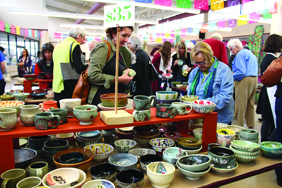 people shopping and stacks of handmade bowls at chili bowl fundraiser