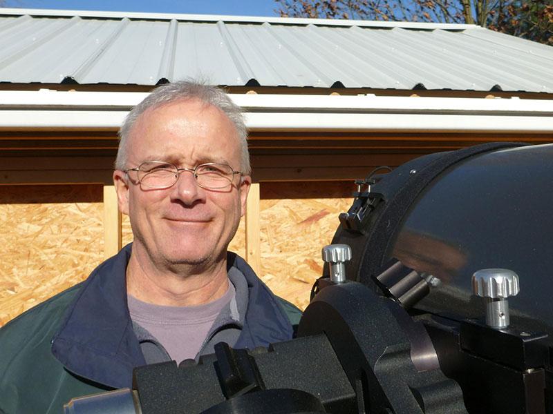 Man smiling next to telescope
