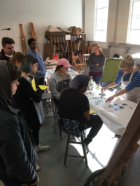 artist jenny nelson painting on table as SUNY Ulster students watch