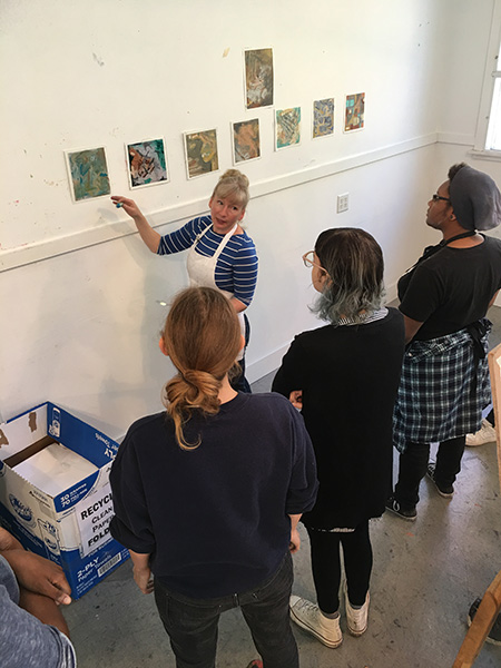 artist jenny nelson discussing paintings on wall as SUNY Ulster students watch