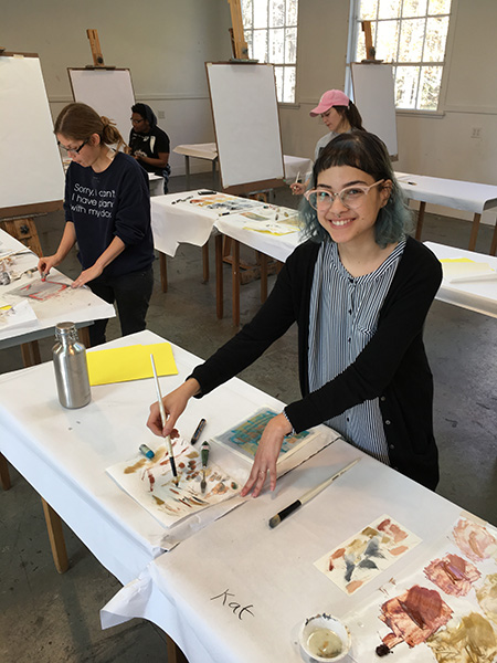Smiling student painting in jenny nelson workshop