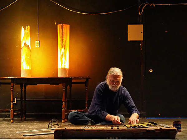 Skip La Plante playing handmade instrument sitting on floor on a stage