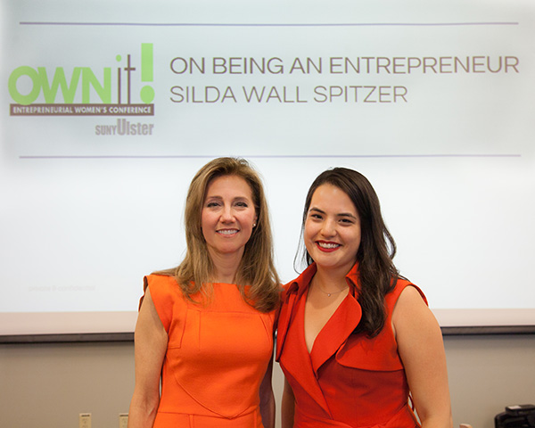Silda Wall Spitzer at Ownit conference with woman in red dress
