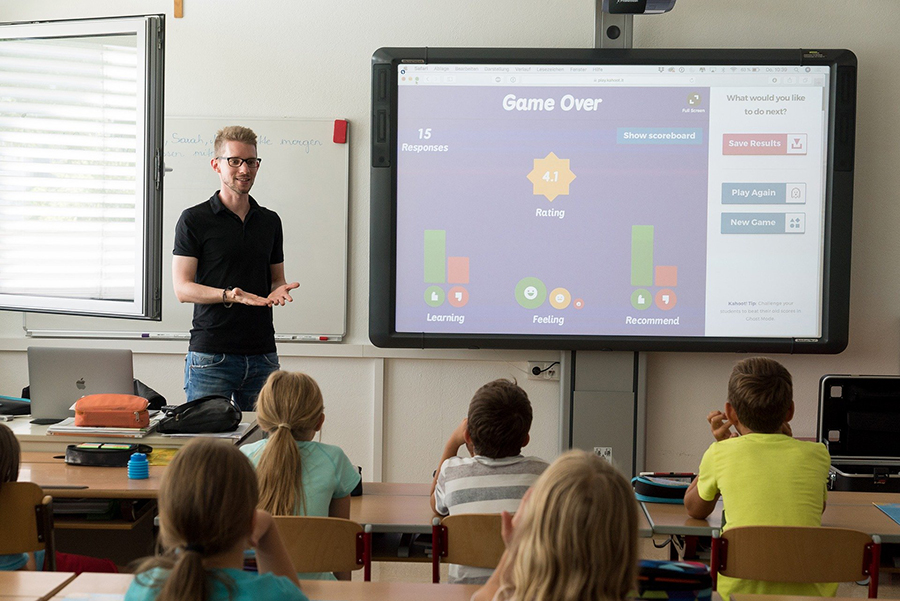 children and educator in classroom with smartboard