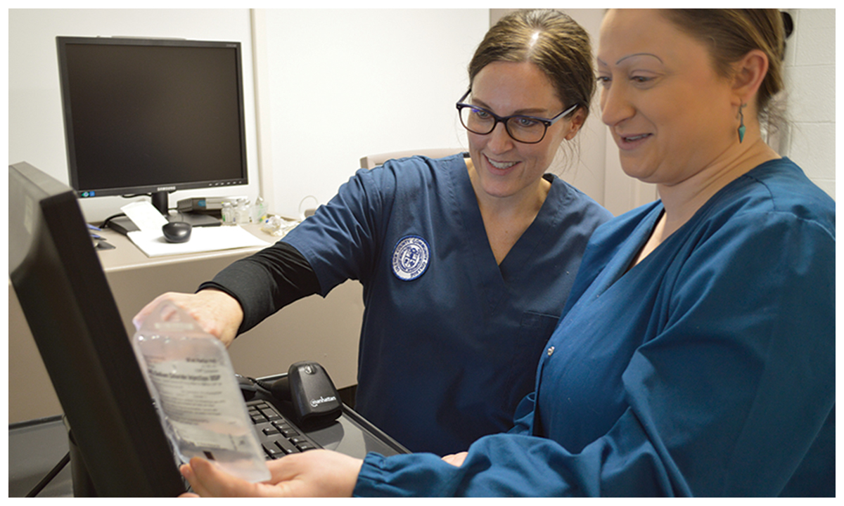 women in scrubs pointing to computer screen