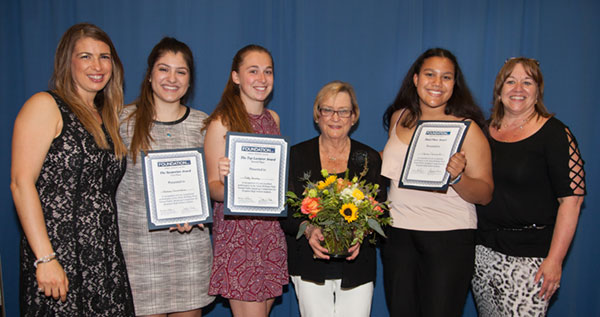 Students holding awards with Anita Williams Peck