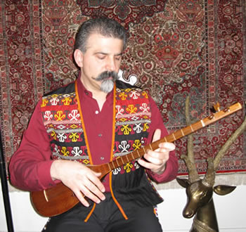 musician in embroidered vest playing instrument