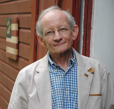 Ted Kooser smiling outside of a house
