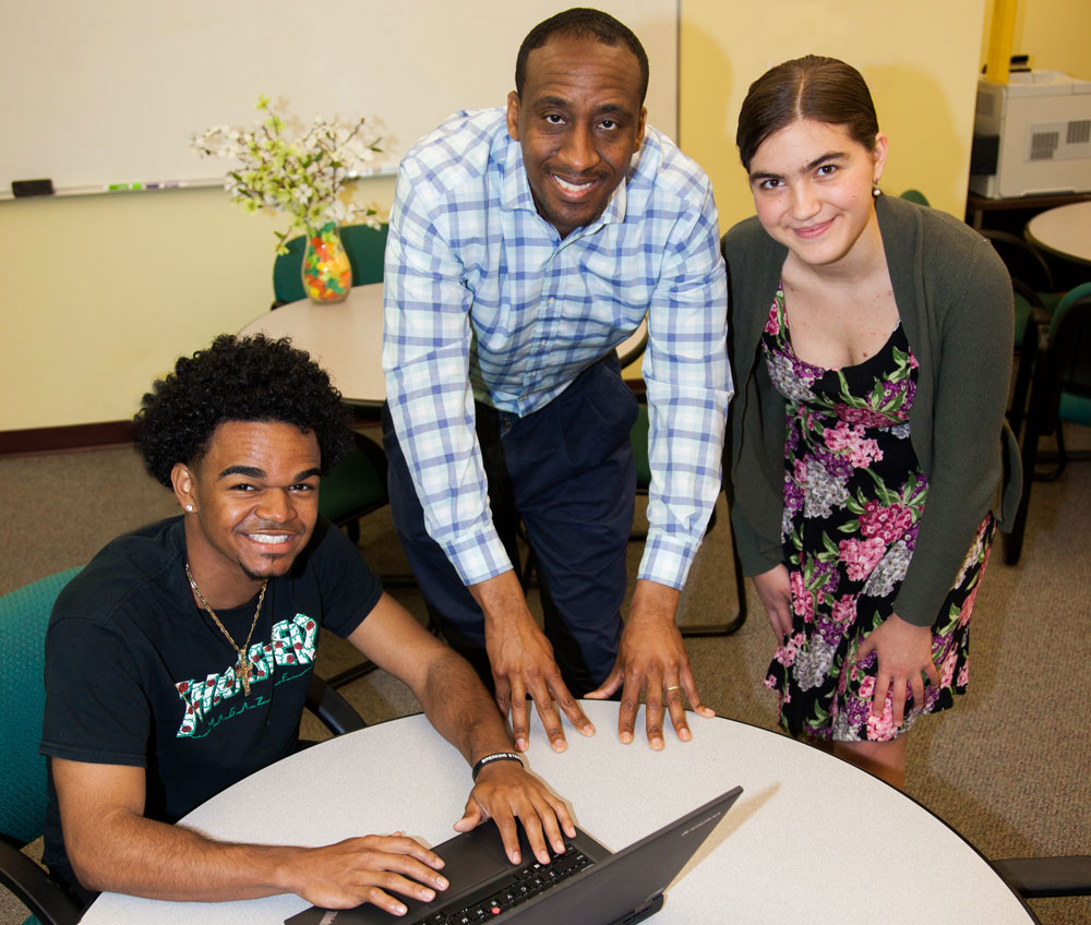 two students with counselor at table with laptop