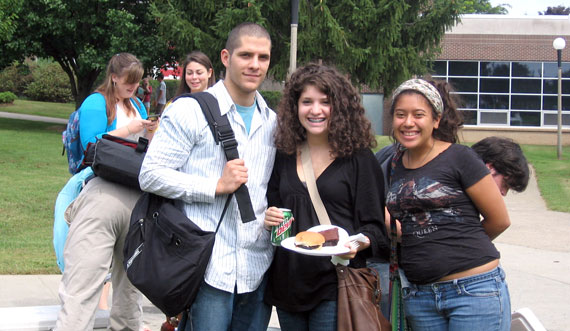 three students smiling outside on campus. one is holding food.