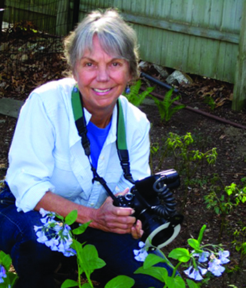 photo of smiling woman, Carol Gracie, in a garden holding a camera