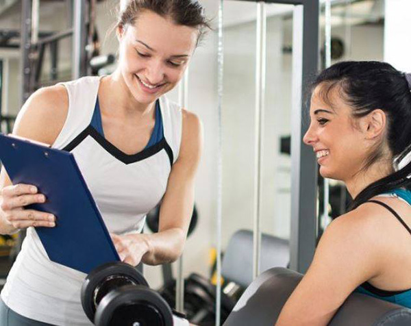 women in gym smiling