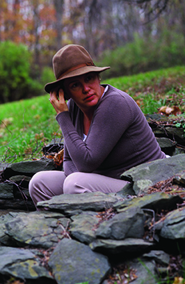 Rebecca Martin, songwriter in brown hat sitting outdoors