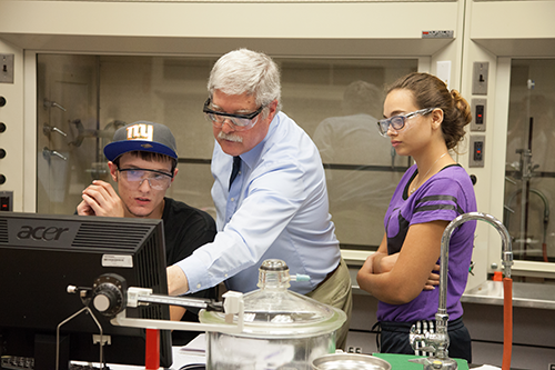 professor and students in safety goggles