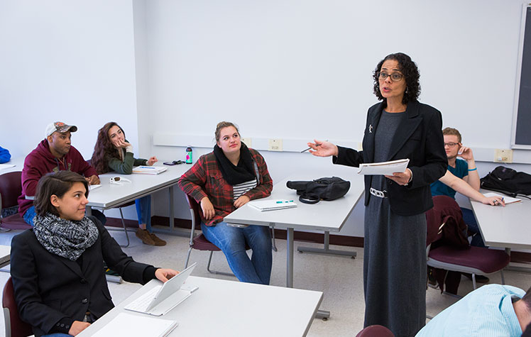 Classroom scene with professor talking while holding notebook and students looking on