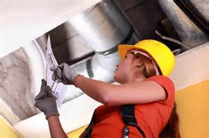 Woman in hard hat working on ceiling ducts